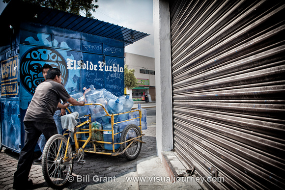 Man pushing cart of empty water bottles in Puebla, Mexico