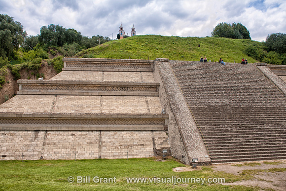 People siting at the top of the reconstructed base of Tepanapa Pyramid's west side.